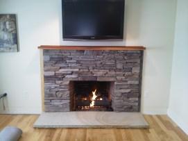 Custom ledge stone veneer with New Hampshire granite hearth