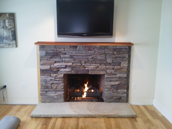 Custom ledge stone veneer with New Hampshire granite hearth