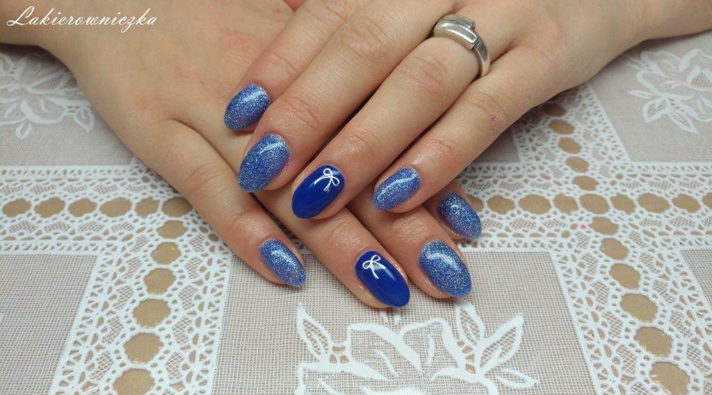 niebieska-brokatowa-hybryda-Rossalind-srebrne-kokardki-naklejki-paznokcie-hybrydowe-Lakierowniczka-niebieska brokatowa hybryda