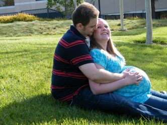 Husband and pregnant wife on grass
