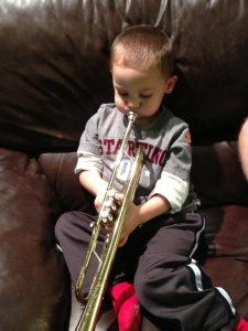 Little boy learning to play a trumpet