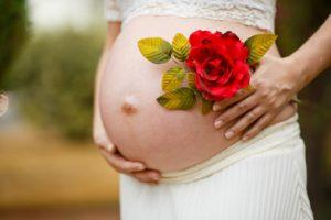 אישה בהריון מחזיקה ורד אדום
