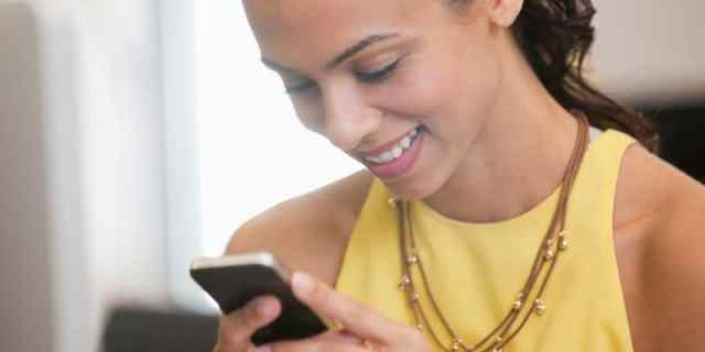 Close up of businesswoman text messaging on cell phone