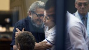 In this photo photo shot through a glass window, Abimael Guzman, founder and leader of the Shining Path guerrilla movement, blue shirt, embraces with an unidentified man as he enters to the courtroom, during his new trial at the Naval Base in Callao, Peru, Tuesday, Feb. 28, 2017. Guzman is being tried for a 1992 car bombing in Peru's capital that killed 25 people and injured 155. The 82-year-old Guzman is already serving a life sentence for the killing of 69 people in the Andean village of Santiago de Lucanamarca in 1983. (AP Photo/Martin Mejia)