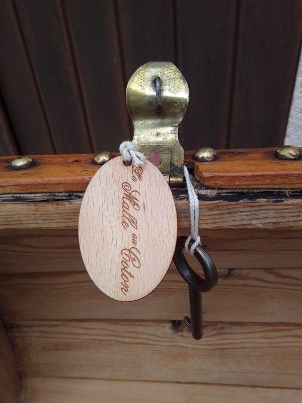Élégante malle de luxe, bombée, en bois clouté. Restaurée. Détail de l'auberon, clef et porte clef en bois gravé La Malle au Coton.