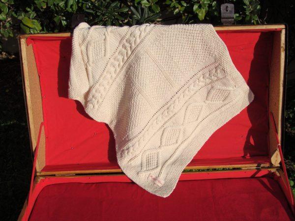 Couverture bébé en coton bio présenté sur une malle ancienne. Création originale : La malle au Coton