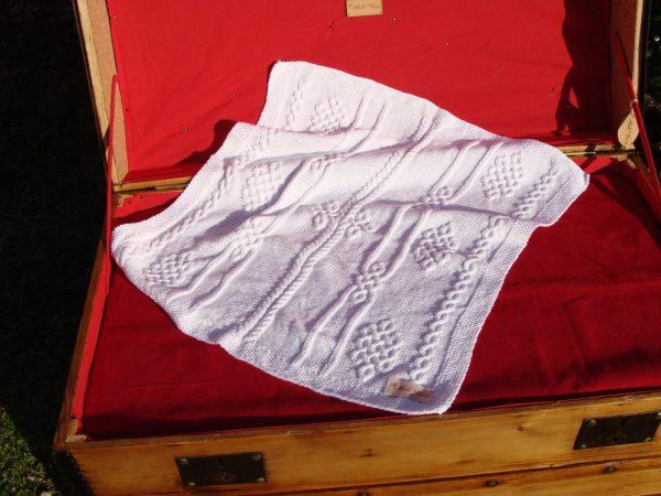 Couverture bébé 100% coton présentée sur une malle ancienne. Création originale : La malle au Coton -W1