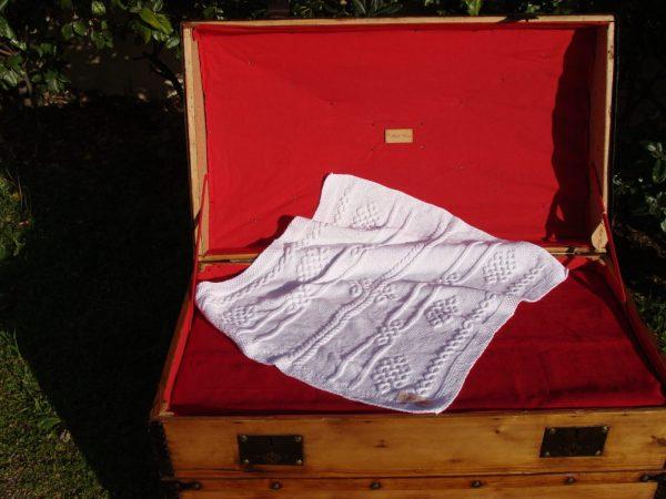 Couverture bébé 100% coton présentée sur une malle ancienne. Création originale : La malle au Coton -W6