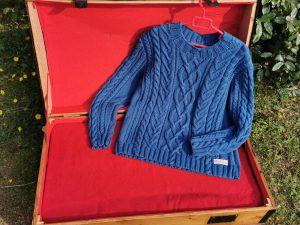 Pull en coton lapis présenté sur une malle ancienne restaurée.