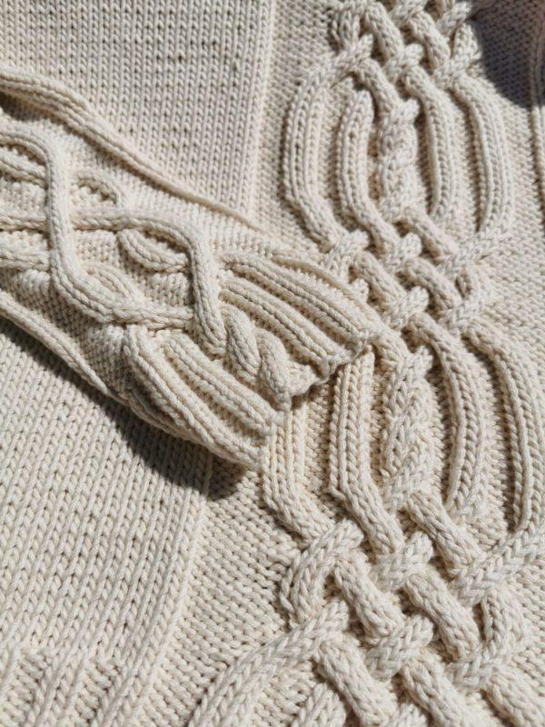 Pull irlandais asymétrique tricoté à la main en coton biologique. Gros plan sur la torsade centrale et un poignet. Création originale La Malle au Coton.
