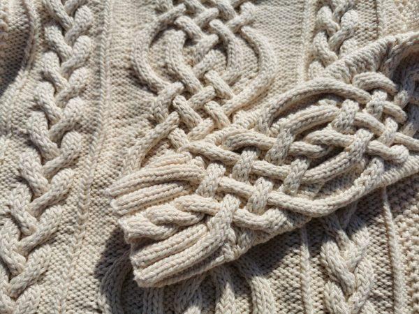 Pull irlandais tricoté à la main à partir d'un fil de coton biologique. Gros plan sur la torsade centrale et les poignets ouvragés. La Malle au Coton