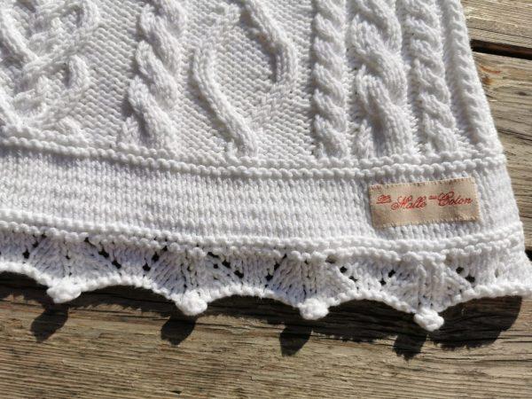 Pull blanc tricoté à la main en coton blanc. Détail de la bordure du bas et de l'étiquette de la marque