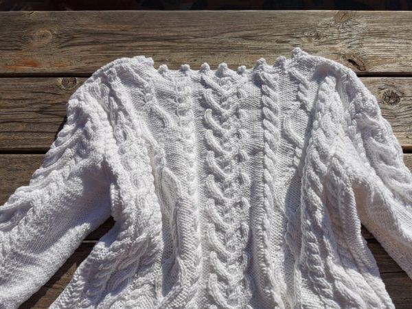 Pull blanc vu de dos sur une table au soleil