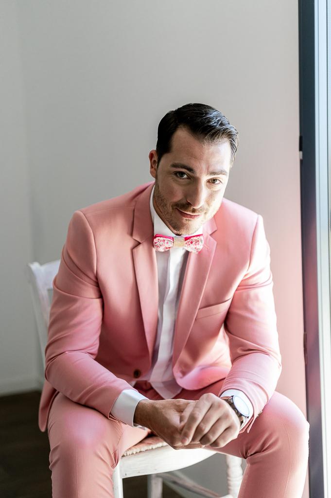 Marié avec un costume rose et noeud papillon rose