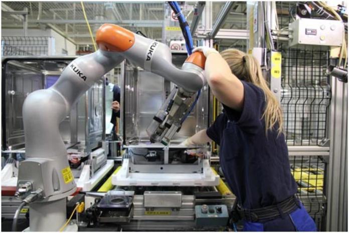 Una obrera manejando un brazo robot