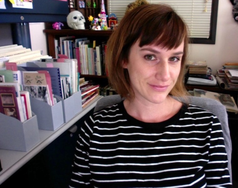 Image of a person in a black striped shirt, sitting in an office chair at a desk in front of archival work.