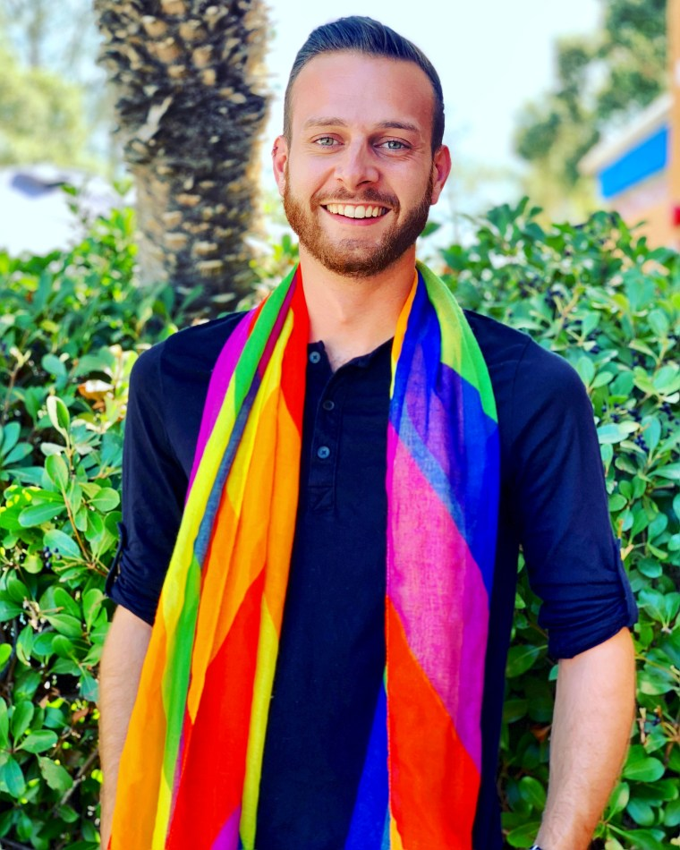 Image of a person in a dark blue button up shirt and a long rainbow scarf, posing and smiling in front of an outdoor scene.