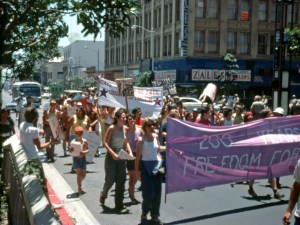 "Photo of people marching down a street, holding up a partly-visible purple banner that reads: ""200 years freedom for--"". Another banner in the background says ""Gays will never be free under capitalism"". The marchers' mouths are open mid-shout."
