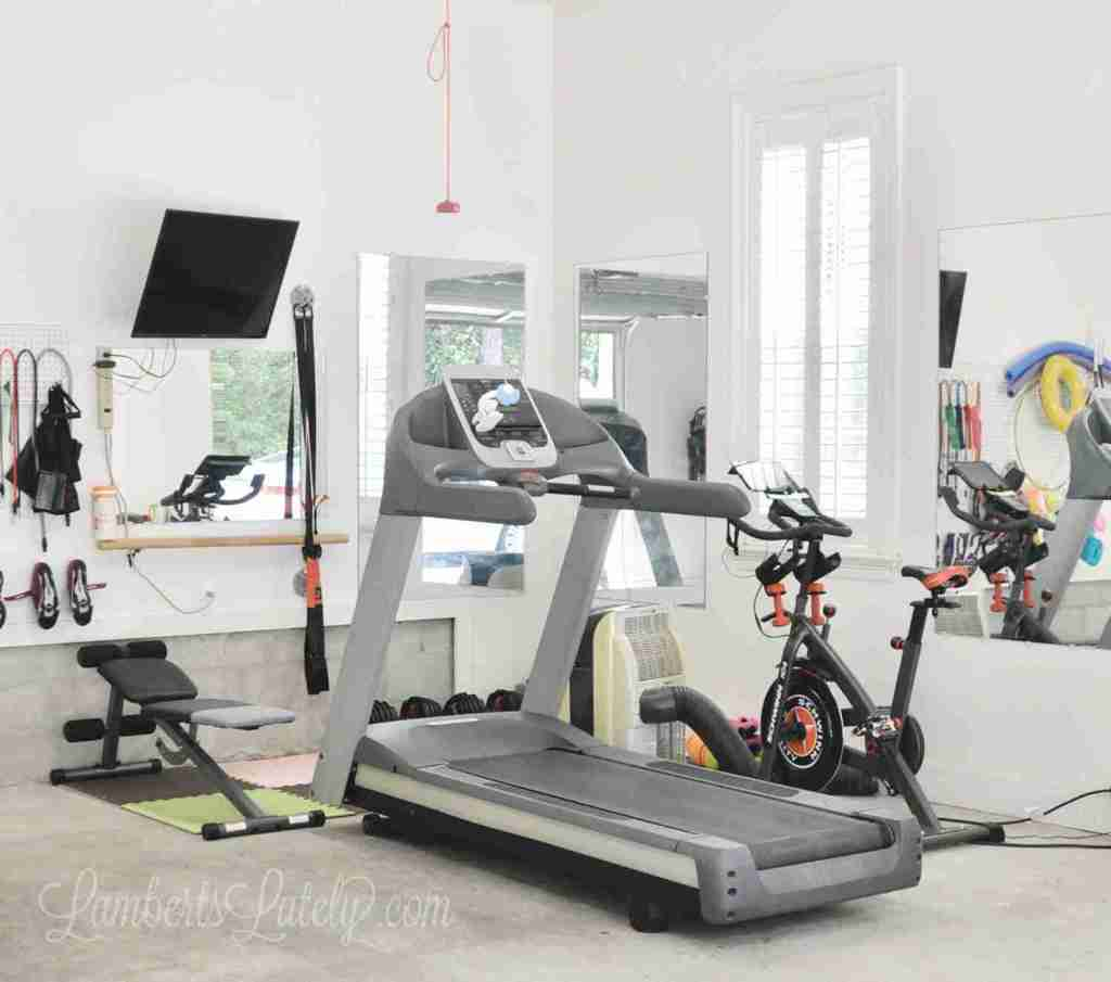 This garage home gym shows how to turn a small space into a functional exercise area. Has a bike, treadmill, strength/weight training area, and TV for Peloton/online workouts.