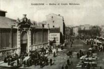 Devant les halles un jour de marché. Outre les commerçants qui envahissent l'ensemble du cours Mirabeau, des étals de marchands des quatre saisons sont situés de part et d'autre de l'entrée des halles dont l'inauguration a eu lieu le 1er janvier 1901. Collection particulière
