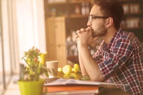 Hombre pensando en su espacio de trabajo simbolizando las personas emocionales y personas racionales