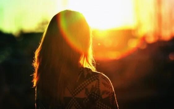 Chica de espaldas al amanecer pensando en afrontar sus problemas