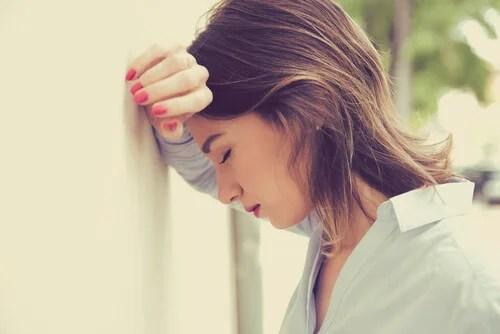 Mujer apoyada en pared tratando de manejar el estrés