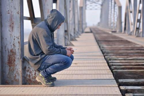 Triste adolescent accroupi qui n'a pas surmonté la période de deuil