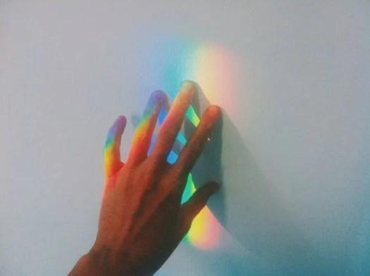 Mano tocando la luz del arco iris