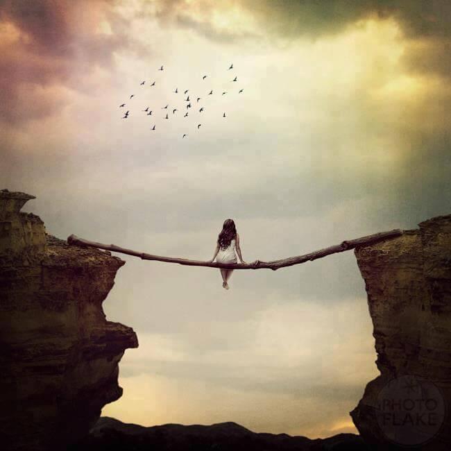Mujer sentada sobre un palo entre dos acantilados