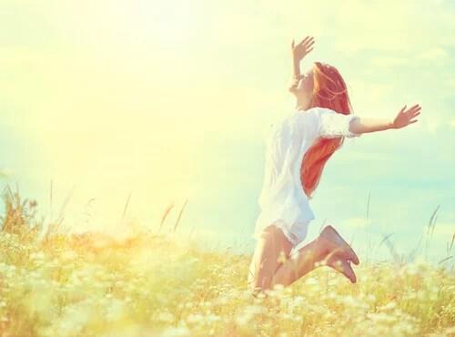 Mujer feliz saltando en el campo