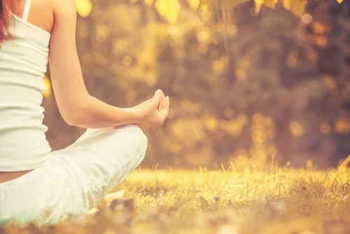 Mujer sentada haciendo meditación