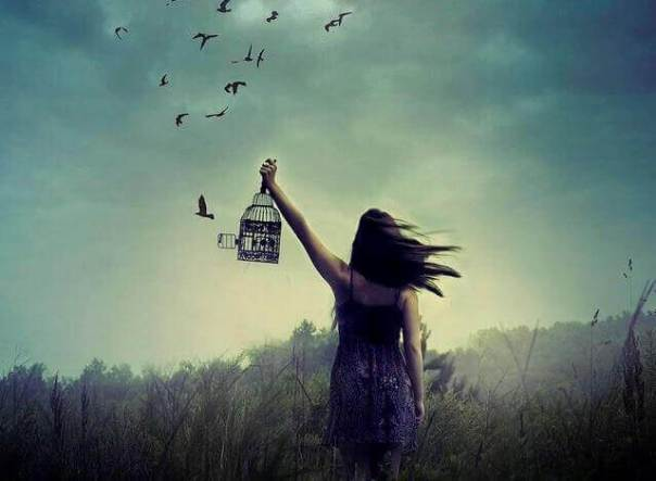 Mujer liberando pájaros de una jaula