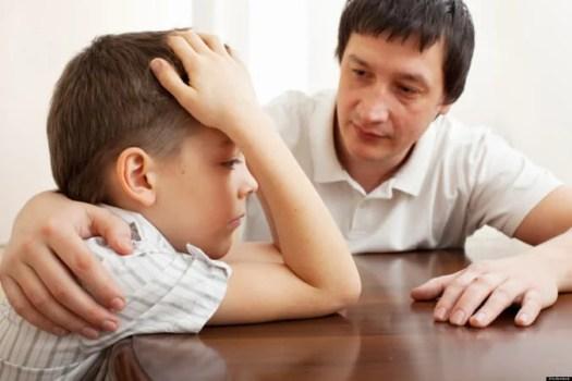 adulto poniendo mano sobre hombro de un niño