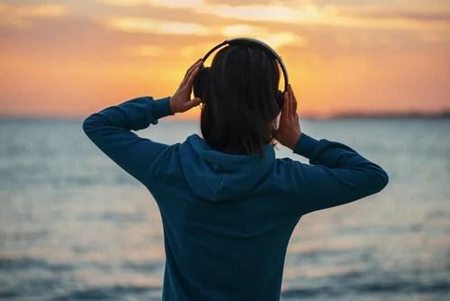 Mujer escuchando música mirando al mar