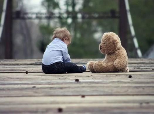 Niño sentando con un oso de peluche