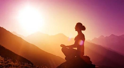 Femme méditant sur une montagne à l'aube essayant de se connecter avec son abondance