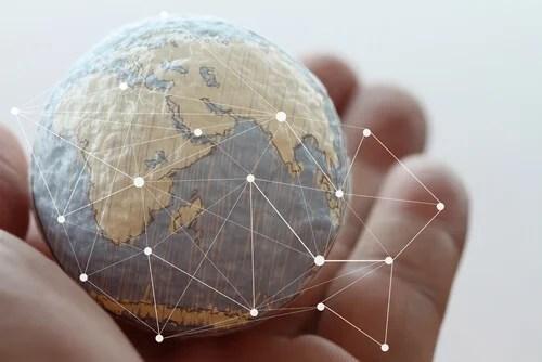 Mano con bola del mundo para representar los países más resilientes