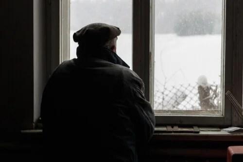 Hombre con alzheimer mirando por la ventana