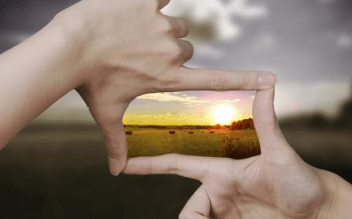 Manos encuadrando una imagen luminosa simbolizando el ejercicio de saborear la vida