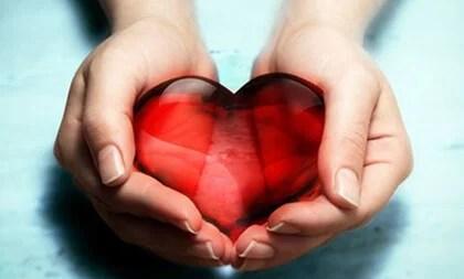 mano con corazón para representar el beneficio de desear que los demás sean felices
