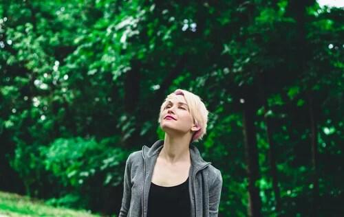Mujer con los ojos cerrados al aire libre para representar el beneficio de desear que los demás sean felices