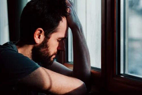 Hombre con ansiedad apoyado en la ventana