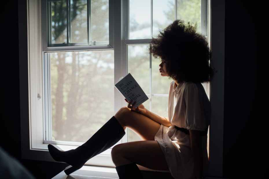 woman sitting on window reading book