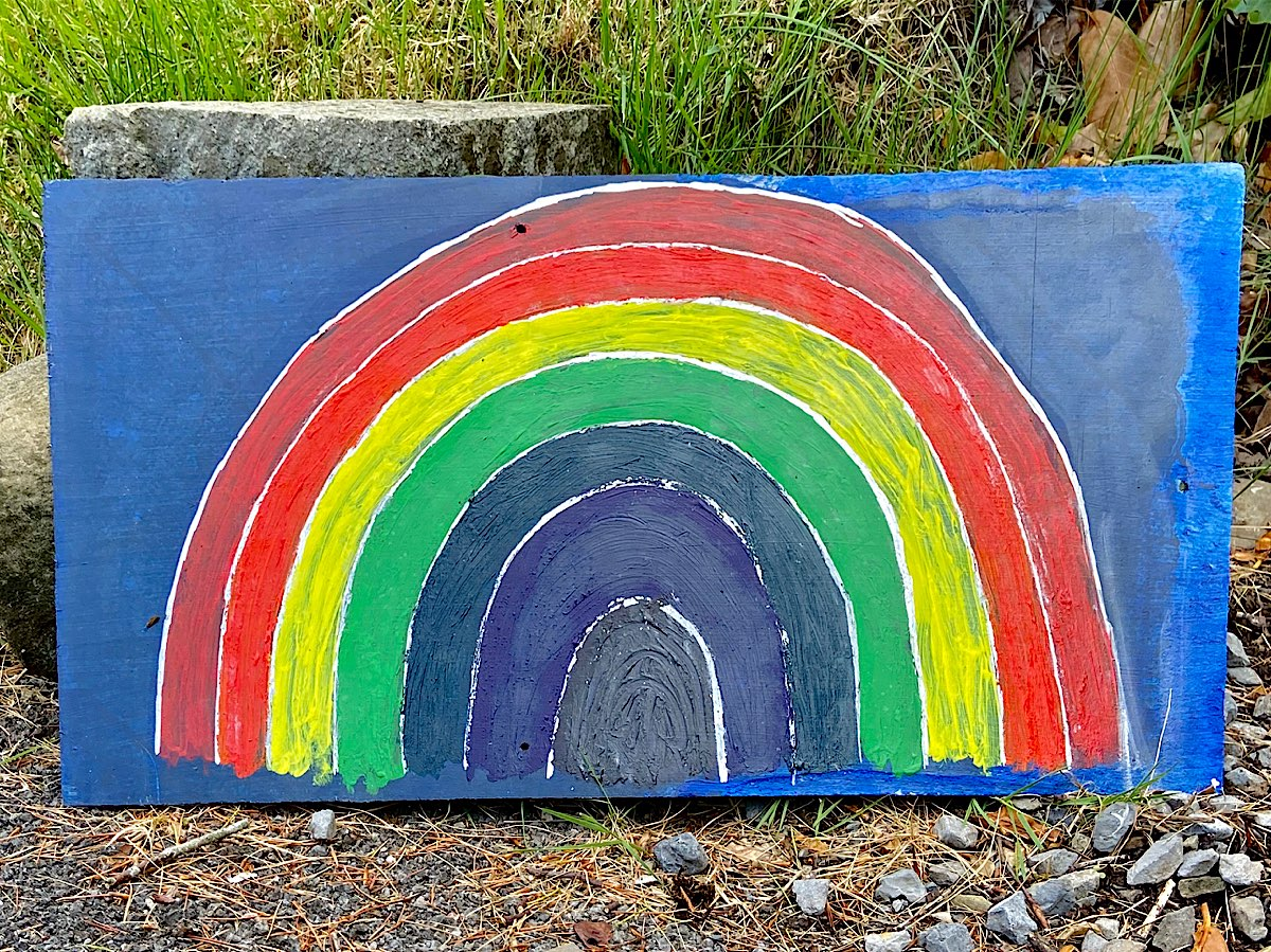 A large rainbow painted onto slate with a midnight blue background