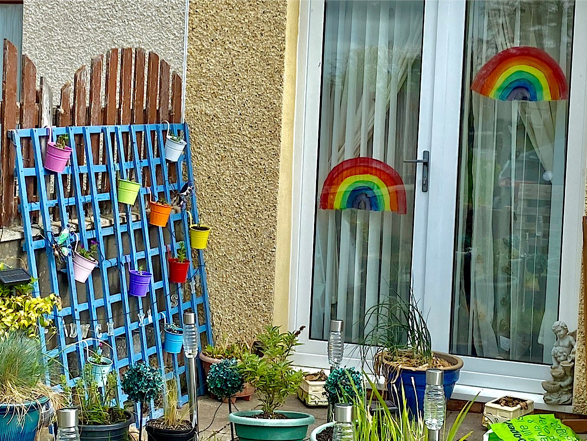 A really colourful picture with a rainbow inside a window looking out onto a trellis hung with multi-coloured plant pots