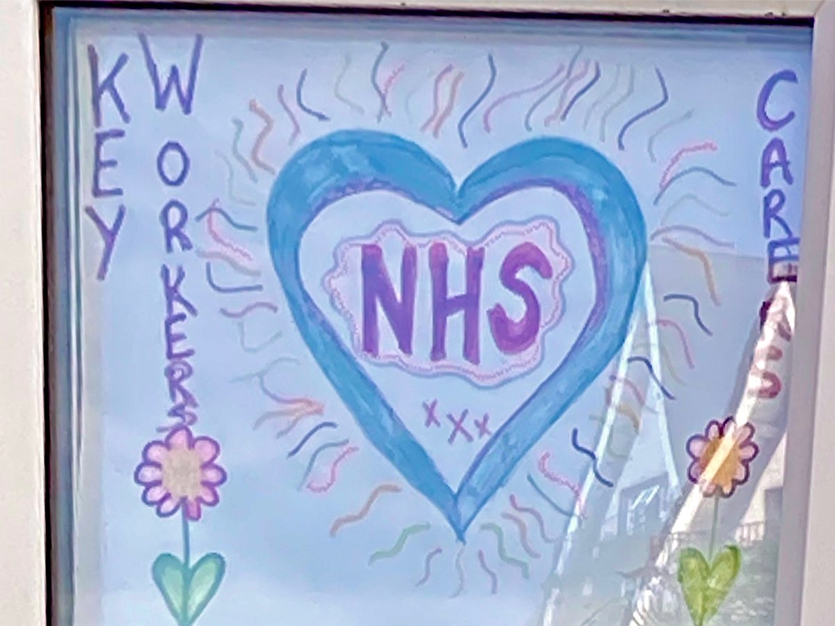This is a big blue and purple heart shape and inside it there's a cloud-like shape and the letters NHS, The heart shape has blue and purple streamers of colour coming out from it and one one side of the page, in vertical lettering it says Kay Workers followed by a flower and on the other side it says Carers followed by a flower.