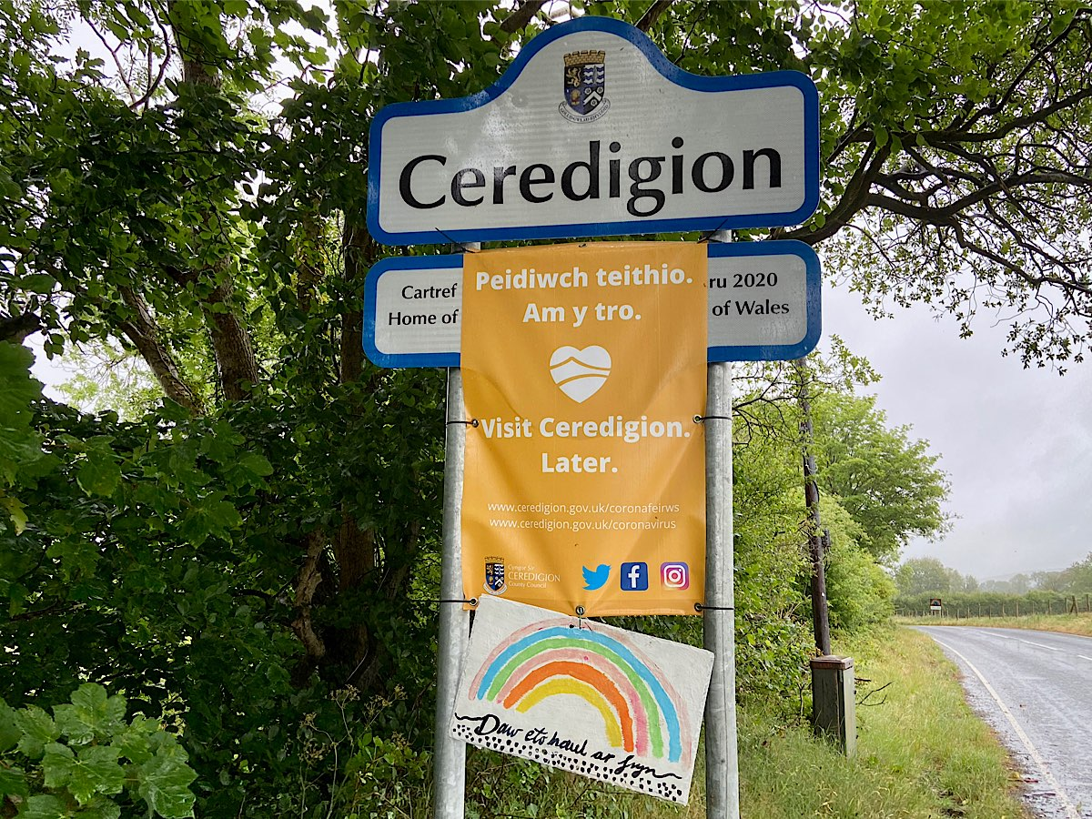 A rainbow painted on white board, says 'daw eto haul ar fryn' underneath and a small heart shaped also rainbow coloured heart sits under the rainbow. It is mounted onto the sign for Ceredigion, underneath a banner that states Ceredigion is closed