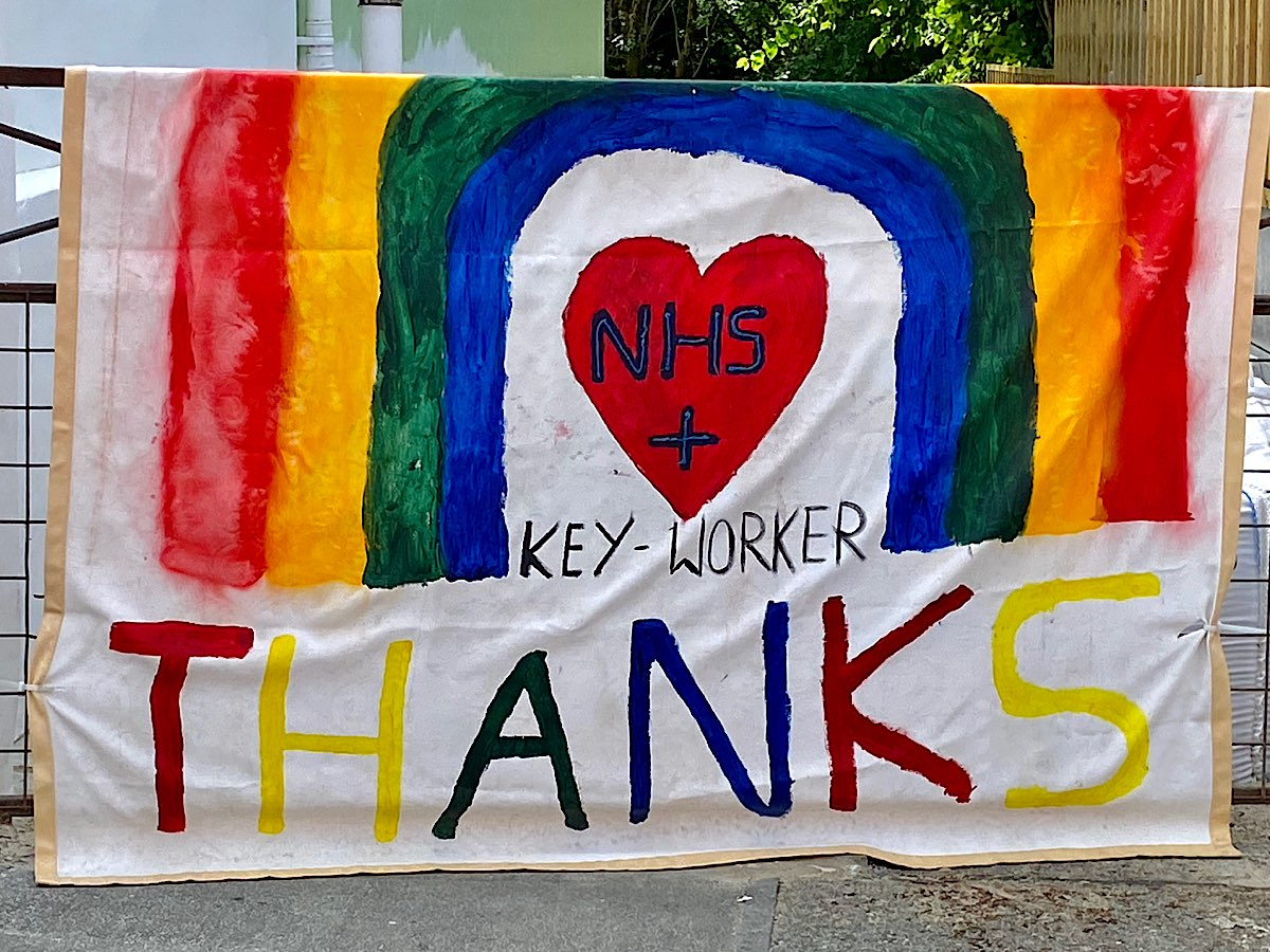 A huge painted banner hanging on a gate post, a 4 colour rainbow with a red heart in the centre that says NHS + key-worker and a huge THANKS at the bottom