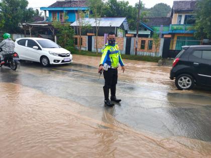 Anggota Satlantas Polres Pringsewu mengatur lalu lintas di ruas jalan yang licin dan tergenang. Foto: Humas Polres Pringsewu